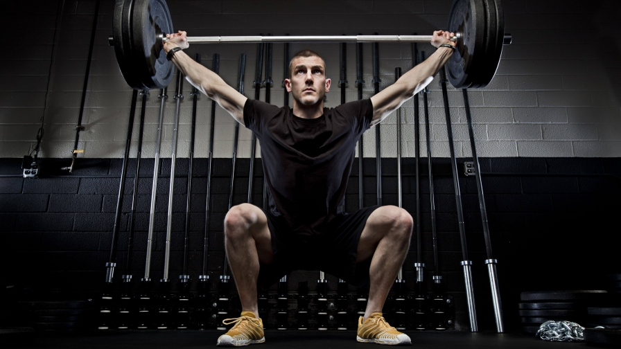 A Young Athletic Man Raises A Heavy Barbells Above His ...