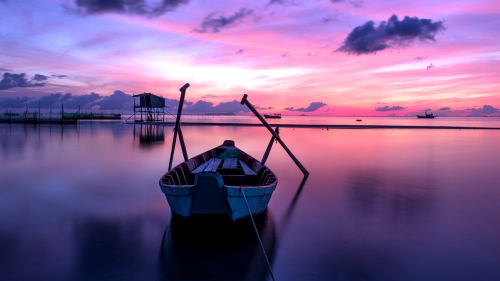 A Boat In Still Waters With Sunrise In The Background Over The Ocean