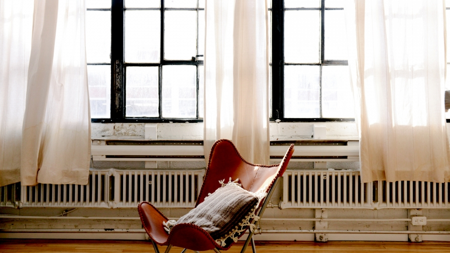 A Brown Leather Chair In An Old Room With Glass Windows And Light Curtains