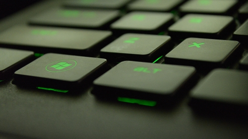 A Closeup Of A Keyboard With Green Symbols And Windows Logo