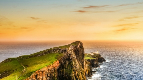 A Light House A Green Hill A Blue Ocean And Orange Sky Nature QHD Wallpaper