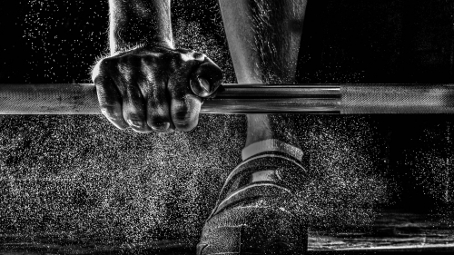 A Man Training Weight Lifting Barbell With Dust Flying Over His Shoes Black And White