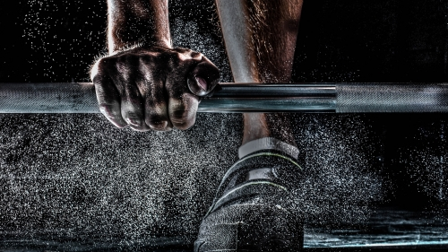 A Man Training Weight Lifting Barbell With Dust Flying Over His Shoes