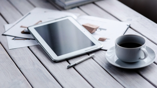 A Table With Tablet Stylus Coffee Cup Pen And Magazine
