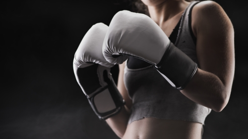 A Woman Getting Ready to Fight Wearing White Boxing Gloves Health UD Wallpaper