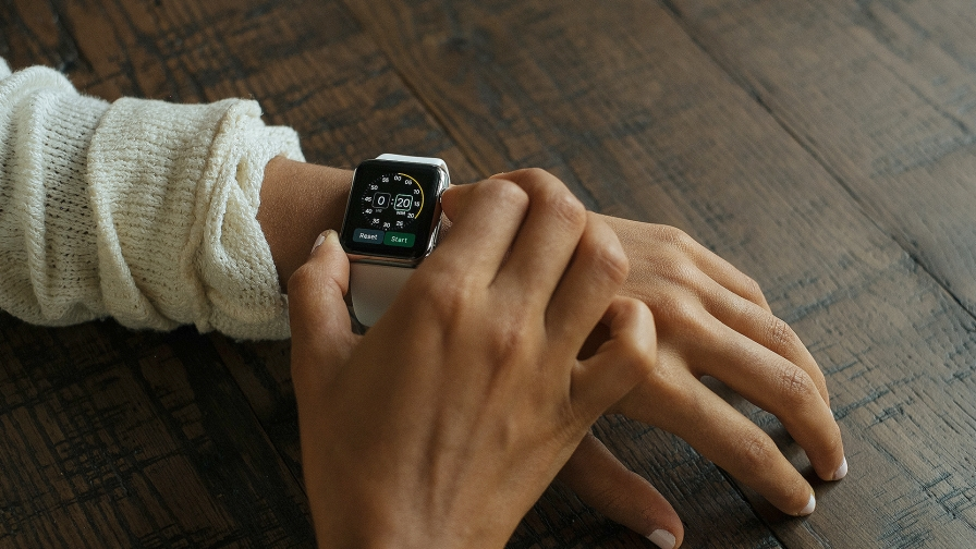 A Woman Looking At Her IWatch Setting Up Stop Watch