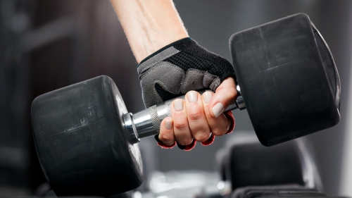 A Woman Wearing Gloves Lifting Dumbells in the Gym Health QHD Wallpaper