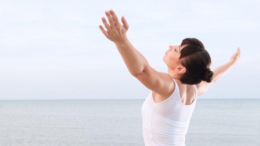 A Young Woman Wearing White Doing Yoga at the Beach UHD Health Wallpaper