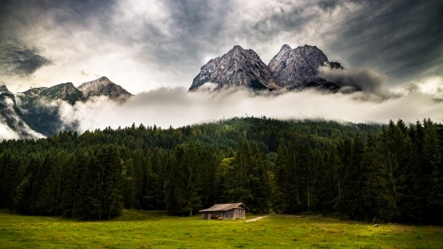 Clouds Rolling Down the Mountain Over a Cottage in the Valley 4K Landscape Wallpaper