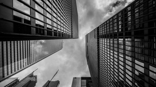 Gray Scale Photo Of Buildings With Glass Window Reflections And Clouds In The Sky